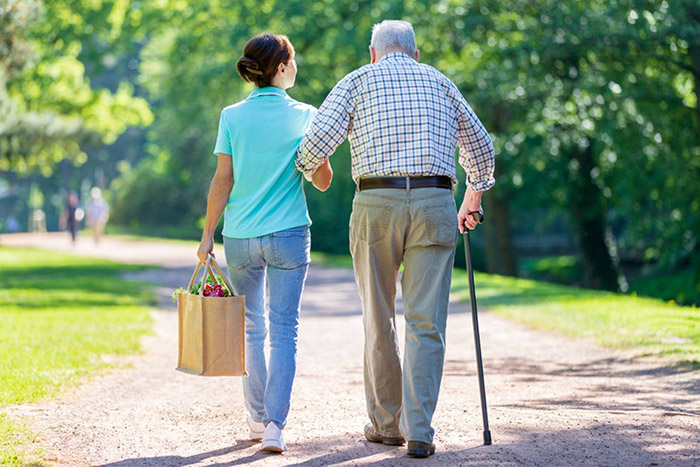 woman helping elderly man carry groceries