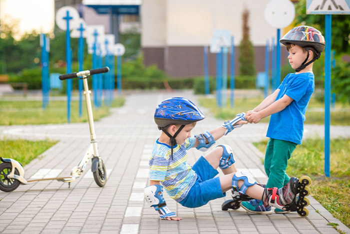 boy helping another boy who fell rollerblading