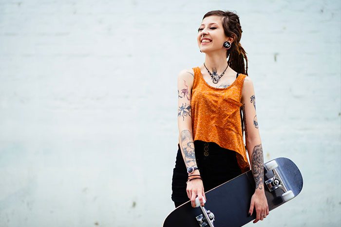 tatooed young woman with skateboard