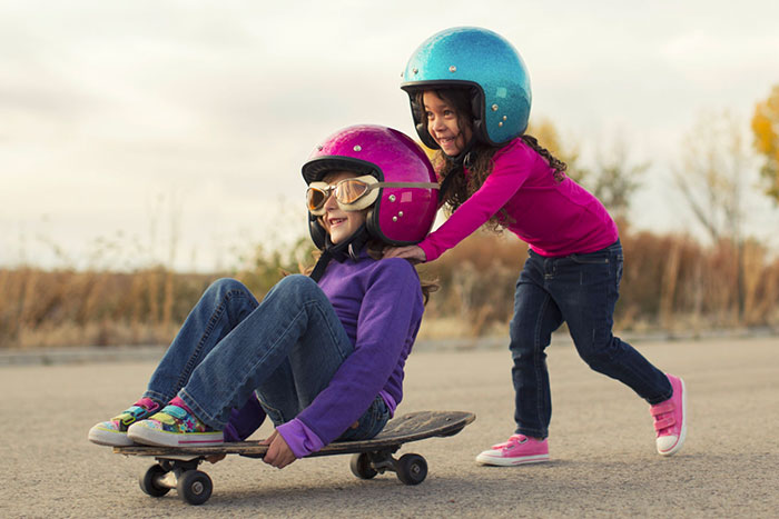girls with helmets and goggles sitting on a skateboard