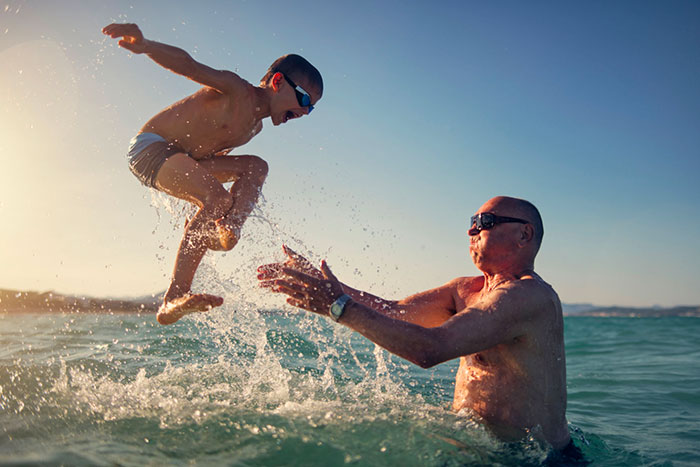 grandfather tossing grandson in the water at the beach